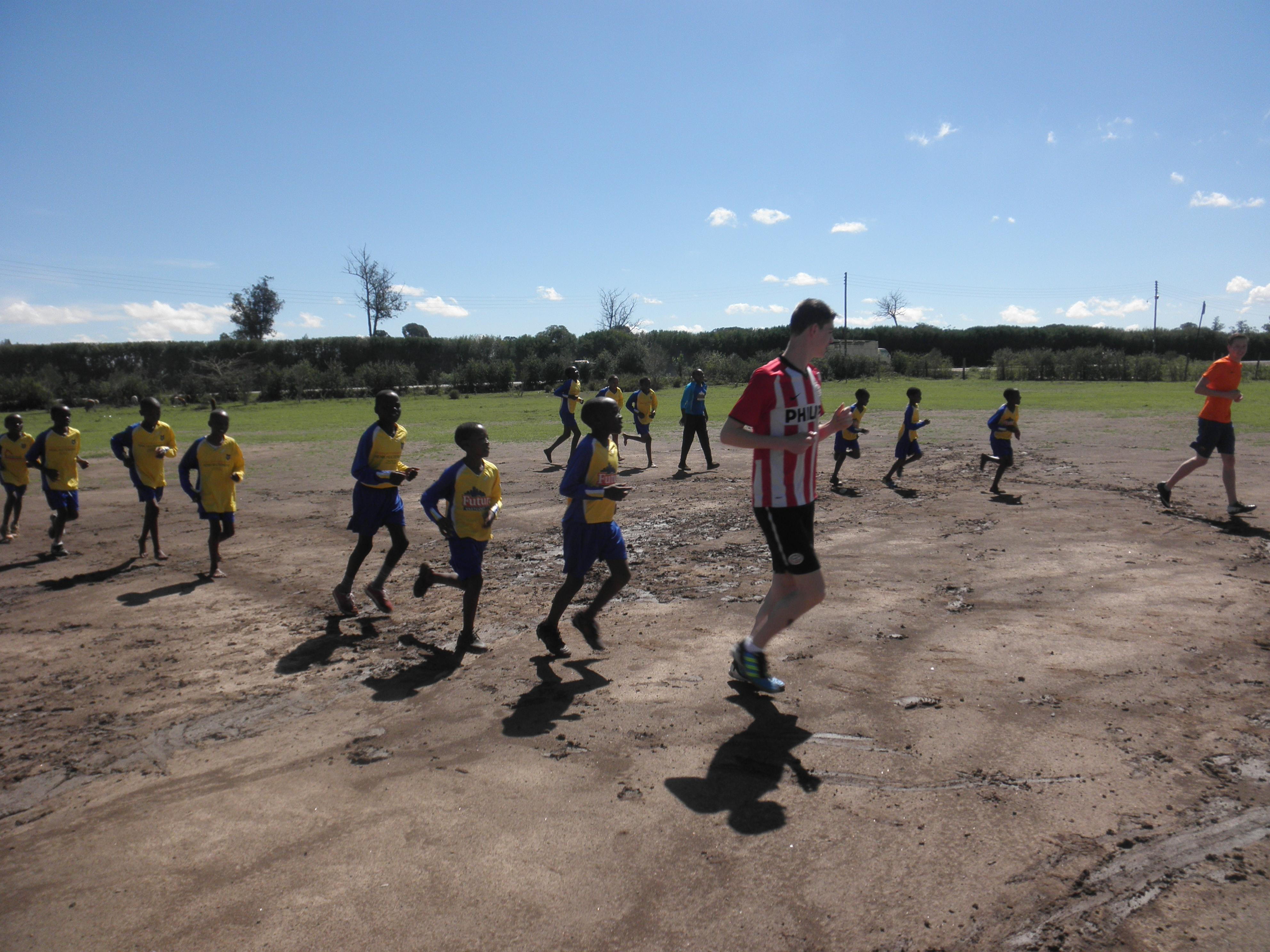A volunteer teaching sports in Kenya teaches children a quick warm up